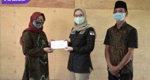 Amaliah Sobli S.KG, MBA, berikan bantuan kepada Kepala Sekolah Madrasah Diniyah Islamiah, Nusweri, didampingi Kades Muara Penimbung Ulu, Mahendra. FOTO : VIRALSUMSEL.COM